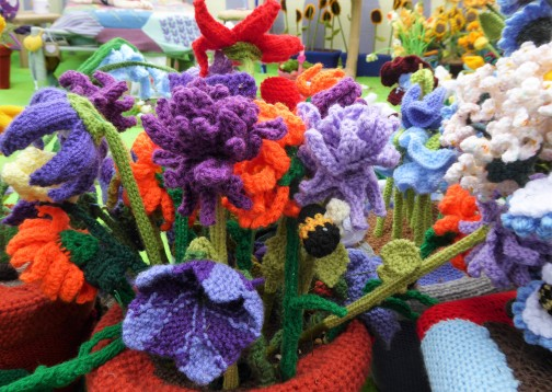 A knitted bee buzzing in the blooms.